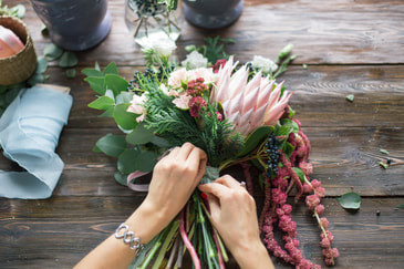 Our hard working florist putting the finishing touches on this bridal bouquet.